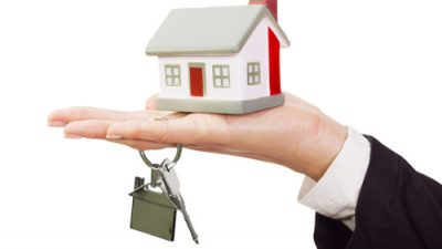 miniature-model-house-and-keys-resting-on-a-female-hand.jpg